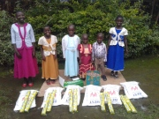 Children sponsored by Mama Linda pausing for a photo in their new clothes and other items they bought